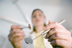 Female dental assistant holding dental mirrorsの写真素材 [FYI02127623]