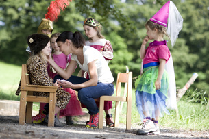 Kindergarten teacher preparing children in costume in a wood kindergartenの写真素材 [FYI02127628]