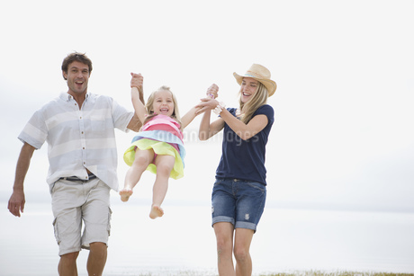 Mother and father swinging girl on beachの写真素材 [FYI02127629]