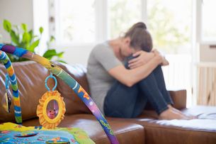 Unhappy Mother Suffering With Post Natal Depression Sits On Sofaの写真素材 [FYI02127679]