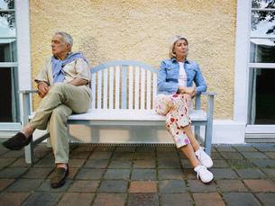 Mature couple sitting apart on a benchの写真素材 [FYI02127690]
