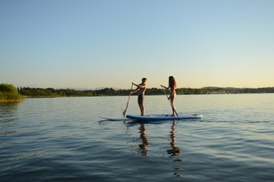 Teenage couple paddle boarding on Lake Starnberg, Bavaria, Germany, Europeの写真素材 [FYI02127706]