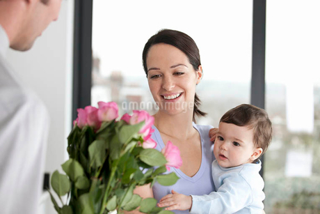 A man giving his partner a bunch of roses, woman holding their baby sonの写真素材 [FYI02127746]