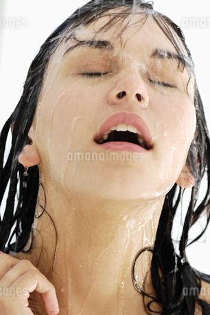 Woman washing face in showerの写真素材 [FYI02127774]