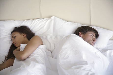 Couple laying with backs to each other in bedの写真素材 [FYI02127784]