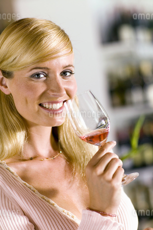 Woman smiling and holding glass of rose wineの写真素材 [FYI02127853]
