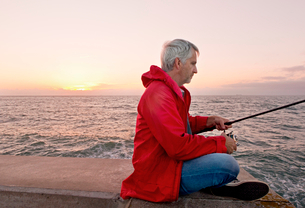 Mature Man Sea Fishing From Jetty As Sun Sets In Backgroundの写真素材 [FYI02127870]