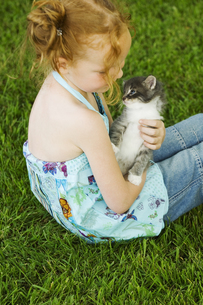 Young girl with kitten in grassの写真素材 [FYI02127900]