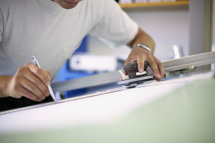 Detail view of man working on a drafting tableの写真素材 [FYI02127904]