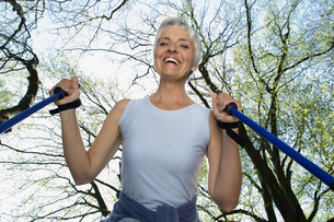 Low angle view of senior woman with walking sticks outdoorsの写真素材 [FYI02127908]