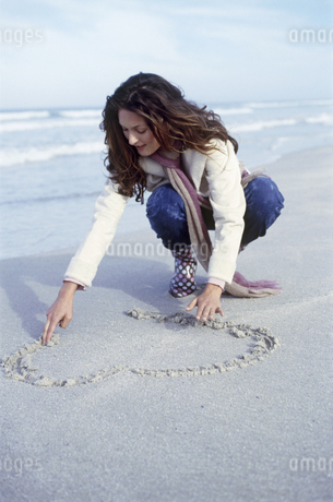 View of a woman drawing a heart in the sand on the beachの写真素材 [FYI02127911]