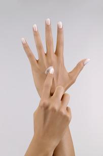 Studio shot of woman applying moisturizer to handの写真素材 [FYI02127932]