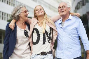 Teenage girl with arms around grandparents in cityの写真素材 [FYI02127953]