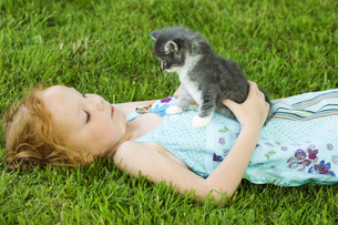 Young girl with kitten in grassの写真素材 [FYI02127956]