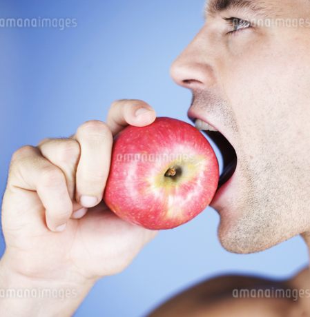 Portrait of a young man eating an appleの写真素材 [FYI02127969]