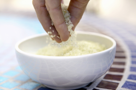 View of a hand scooping bath salts out of a bowlの写真素材 [FYI02128088]