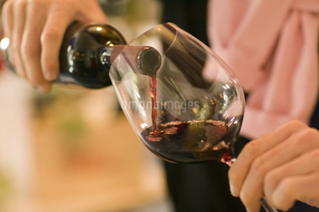 Close up of man pouring red wine indoorsの写真素材 [FYI02128113]
