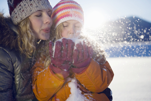 Mother and girl blowing snowの写真素材 [FYI02128115]