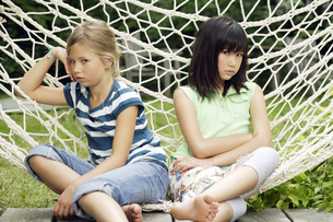 Young girls in hammock ignoring each otherの写真素材 [FYI02128121]