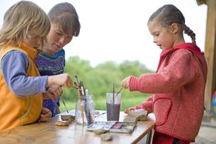Kindergarten teacher painting with kids in a wood kindergartenの写真素材 [FYI02128127]