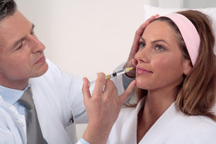 Woman receiving anti-aging injection in faceの写真素材 [FYI02128134]