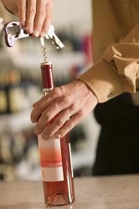 Close up of man opening bottle of wineの写真素材 [FYI02128179]