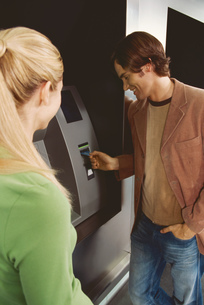 Couple using an automated banking machineの写真素材 [FYI02128193]