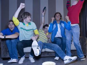 Group of men cheering on sofaの写真素材 [FYI02128209]