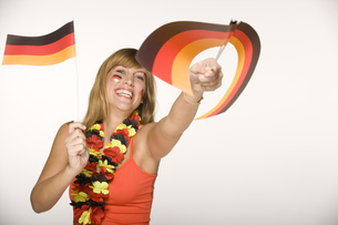 Young woman waving German flagsの写真素材 [FYI02128217]