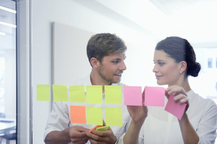 Young office workers organizing and planning with adhesive notes in officeの写真素材 [FYI02128228]
