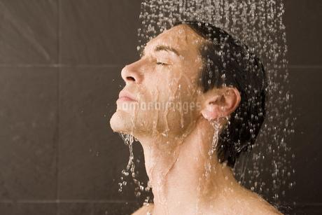 Man standing under water in showerの写真素材 [FYI02128231]