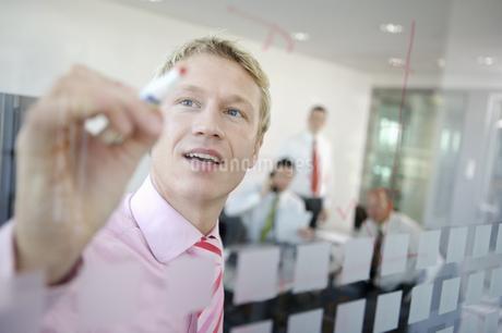 Businessman writing on dry erase boardのイラスト素材 [FYI02128236]