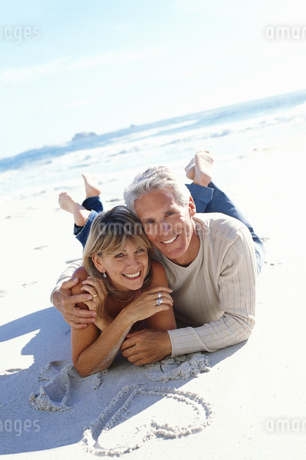 Mature couple lying on the beach, heart drawn in sandの写真素材 [FYI02128257]