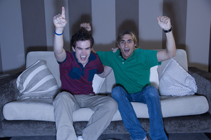 Two young men cheering on sofaの写真素材 [FYI02128265]