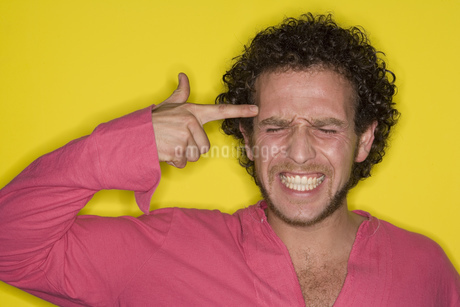 Man mimicking gun with hand pointed at headの写真素材 [FYI02128270]