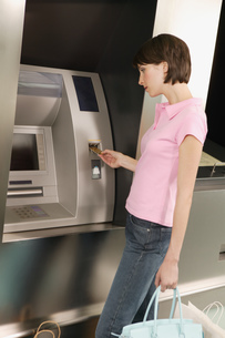 Female shopper using an automated banking machineの写真素材 [FYI02128280]