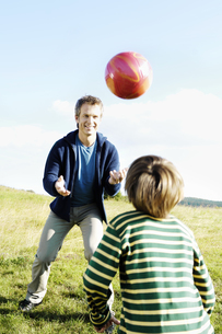 Father and son playing football outdoorsの写真素材 [FYI02128288]