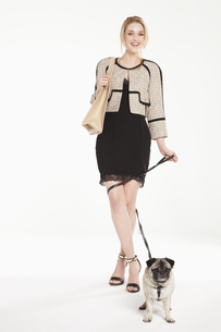 Glamorous young woman with pet pug, portraitの写真素材 [FYI02128301]