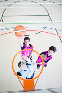 High school students playing basketball in gym classの写真素材 [FYI02128324]
