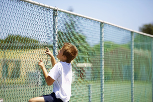 View of young boy climbing chain link fenceの写真素材 [FYI02128338]