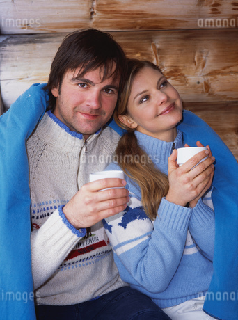 Couple wrapped in blanket with coffeeの写真素材 [FYI02128439]