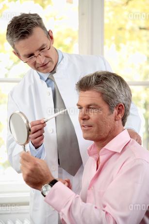 Plastic surgeon examining male patientの写真素材 [FYI02128458]