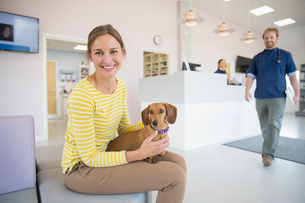 Pet dog owner in vet surgery waiting room reception smiling at cameraの写真素材 [FYI02128530]