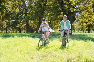 Senior couple, mountain biking, in treelined fieldの写真素材 [FYI02128620]
