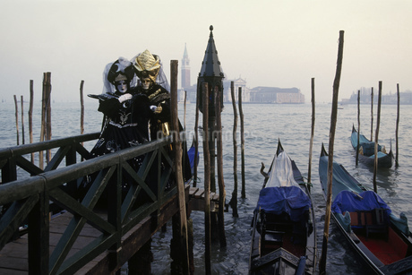 Costumed Carnival participants and boats in Venice, Italyの写真素材 [FYI02128686]