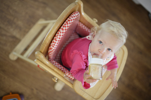 Baby drinking from bottle in highchairの写真素材 [FYI02128695]