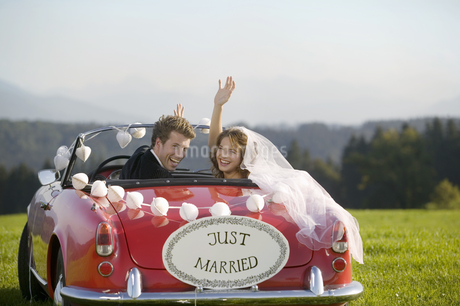 Newlyweds driving car in fieldの写真素材 [FYI02128712]