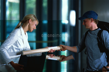 Young male courier handing delivery to receptionistの写真素材 [FYI02128714]