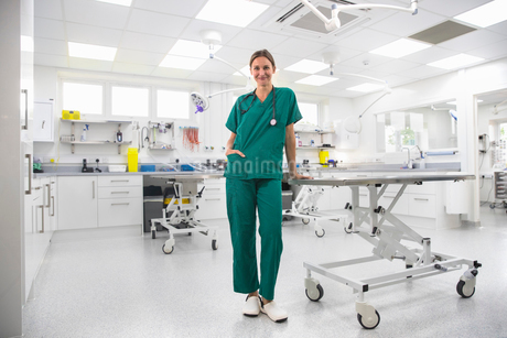 Nurse by table in examination room of vet surgery smiling at cameraの写真素材 [FYI02128725]