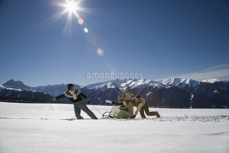 Man pulling friends on sled, Luesener Alm, Dolomite Alps, South Tyrol, Italyの写真素材 [FYI02128763]